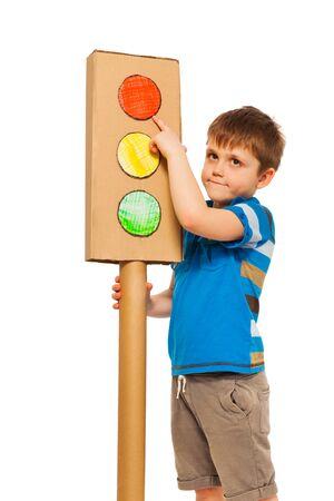 semaforo peatonal: Muchacho que estudia las normas de tráfico, apuntando a la luz roja de cartón modelo de luces, aislado en blanco