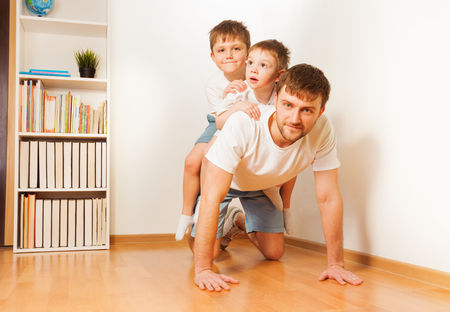 piggy back: Father giving his two kid sons piggy back ride at home