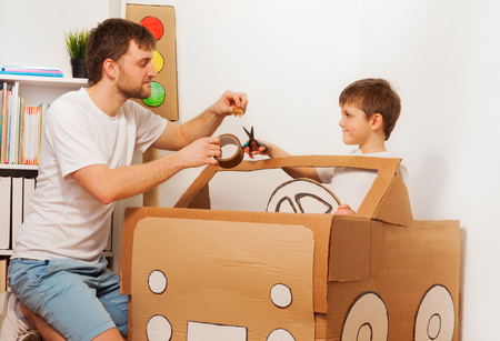 scotch tape: Dad helping his kid son to cut piece of sticky tape for fixing it to big toy cardboard car at home