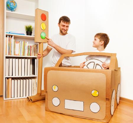 段ボール車自宅でドライバーを演奏として、緑色の光信号を指している、息子に交通法規を説明するお父さん 写真素材