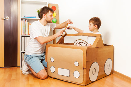 Father and his son making toy car, cutting sticky tape to fix it to big cardboard box
