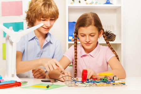 experimento: Dos hijos adolescentes, chico y chica, creando modelo de turbina del generador de viento de trabajo en la clase de física