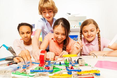 experimento: Cuatro de varios estudiantes adolescentes étnicos que a las pruebas físicas con el circuito eléctrico en el laboratorio