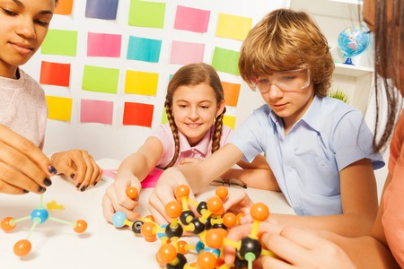 boy 15 year old: Young students, boy and girls, assembling molecule model at the laboratory