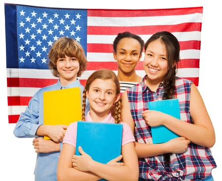 Four happy multiethnic teenage students standing against American flag, holding textbooks, isolated on white