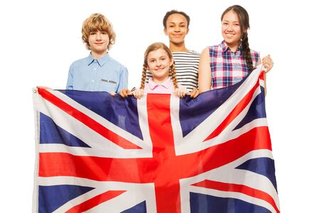 Four multiethnic teenage kids standing behind British flag, isolated on white background Stock Photo