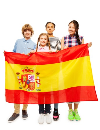 boy 15 year old: Group of four happy multiethnic teenage kids standing behind the flag of Spain, isolated on white