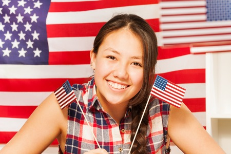 13: Smiling teenage Asian girl with two flags of United states of America