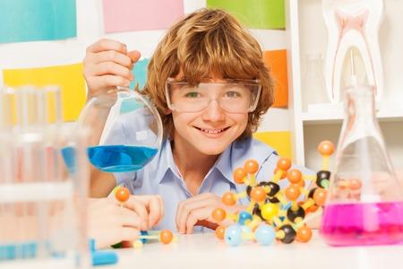 el atomo: El muchacho joven en gafas de seguridad que sostiene matraz con el reactivo azul en el laboratorio químico