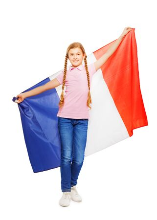 13 15 years: Smiling teenage girl with two long plaits holding unfolded French flag behind her back, isolated on white