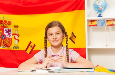 plaits: Cute schoolgirl with plaits, holding two Spanish flags in her hands, sitting at the desk