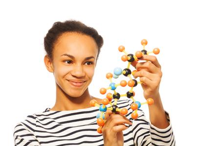 molecula: niña africana estudio de la estructura molecular, la celebración de modelo de plástico en sus manos, aislado en blanco