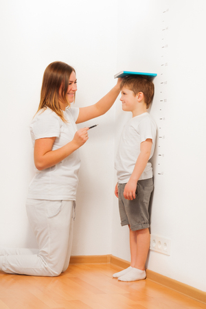 height chart: Mother checking her sons height on growth chart, as kid standing near the white wall, by using a book and a pen Stock Photo