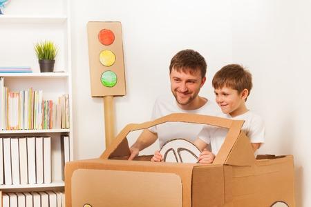 장난감 손으로 운전하는 행복 한 아이 소년과 그의 아버지는 방에서 종이 자동차를 만든