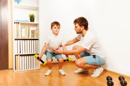 squats: Cheerful father teaching kid son to squats with dumbbells at home Stock Photo