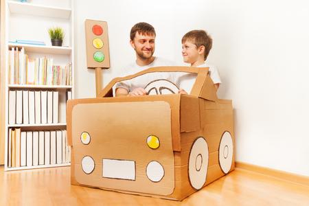 父亲和他的儿子驾驶手工制作的纸板汽车在房间里