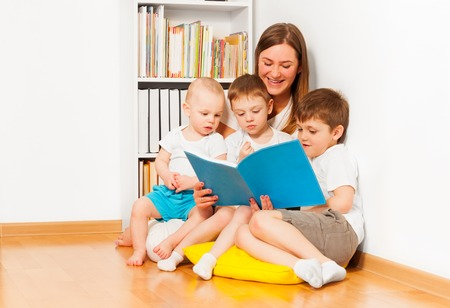 Young mother reading book to her three age-diverse kids, sitting on yellow pillow against white wall and bookshelf at the room Stock Photo