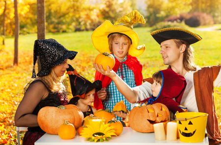 Family in Halloween costumes with Jack-O'-Lantern pumpkin sitting at the table outside during beautiful sunny autumn day
