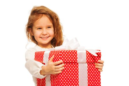 5 year old girl: Girl with huge red birthday present standing isolated on white Stock Photo
