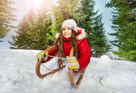 skids: Happy girl with warm hat, hand gloves and scarf having fun on snow sledge, outdoors