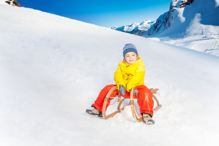 Little boy slide down the hill in the mountain on sledge Stock Photo