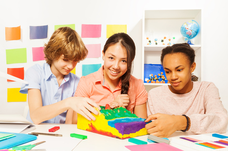 13 year old boy: Three multi ethnic students modeling surface relief with plasticine at the geography lesson