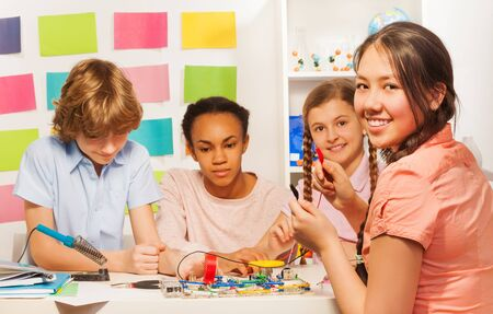 school board: Four multi ethnic teenage students creating electric chain model at physics lesson