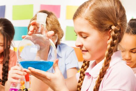 13 15 years: Schoolgirl holding flask with blue reagent at the chemistry classroom Stock Photo