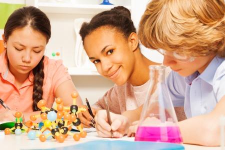 atomo: Tres estudiantes étnicos multi que escribe fórmula química que se sienta en el escritorio en la clase de ciencias