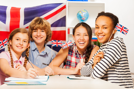 Four multiethnic teenage students sitting at the desk, holding British flags at the language courses Stok Fotoğraf