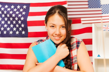 red white blue: Pretty teenage Asian girl with textbook against the flag of United states of America