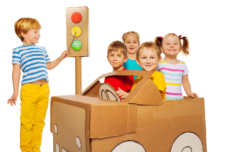 cartoon child: Five happy preschoolers, boys and girls, studying traffic regulations looking to the caution signal of toy cardboard light, isolated on white