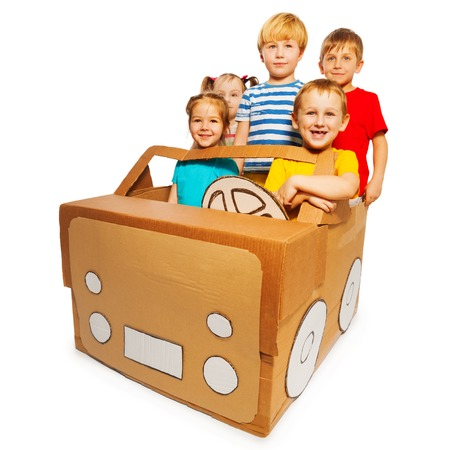 preschoolers: Picture of five happy preschoolers driving toy handmade cardboard car, isolated on white background Stock Photo
