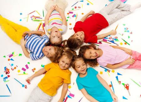 five years old: Close up picture of funny five years old kids laying among school office supplies, making a circle Stock Photo