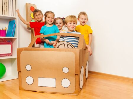 drive car: Five smiling kids, boys and girls, driving handmade cardboard car at the kindergarten class