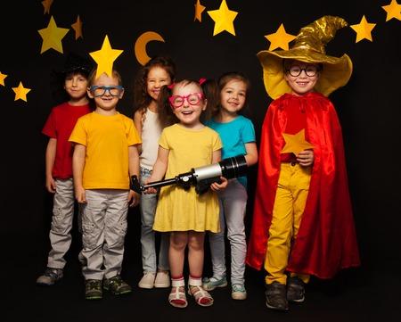 Groep van zes jongens en meisjes in sterrenkijkers kostuums te kijken handgemaakte sterren en de maan tegen zwarte achtergrond