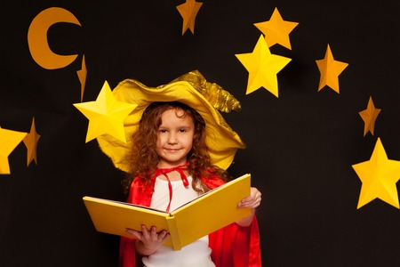 the watcher: Little girl in sky watcher costume studying constellation of stars, holding big book with copy space at the night sky background