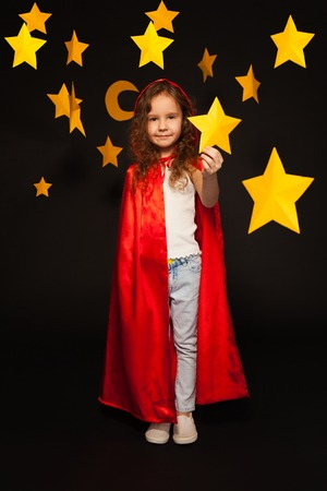 yellow star: Full length picture of little girl in red cape with hood, holding big yellow paper star in her hand, standing against black background Stock Photo