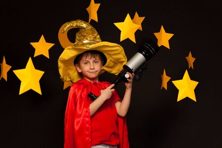 the watcher: Five years old boy in sky watcher costume with telescope among handmade paper stars