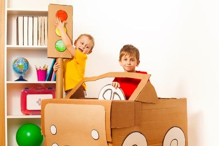 Twee 5 jaar oude jongens studeren verkeersregels met speelgoed karton licht en auto