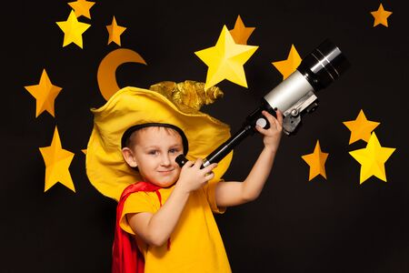 the watcher: Little boy in sky watcher costume looking through a telescope among big handmade stars and moon