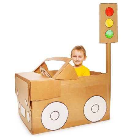 sit: Little boy driving his handmade cardboard car, isolated on white background