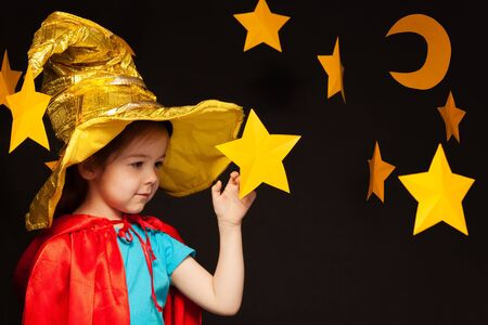 five years old: Beautiful five years old girl playing sky watcher with handmade stars and moon against black background Stock Photo