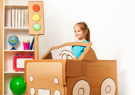 pretend: Cute little girl driving her toy cardboard car at the kindergarten