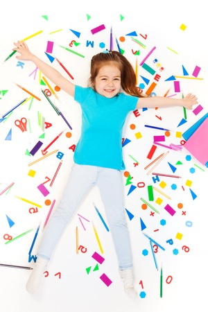 five years old: Happy five years old girl laying among heap of colored stationery, top view Stock Photo