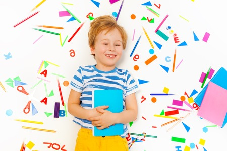 colored school: Top view of smiling five years old boy holding textbook and laying among the heap of colored school office supplies