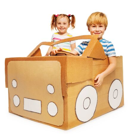 pretend: Cute five years old kids, boy and girl, playing the driver and the passenger with cardboard car, isolated on white