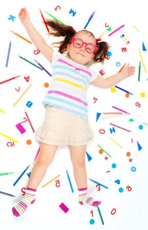 office supplies: Top view of funny girl with pink glasses laying among school office supplies, isolated on white