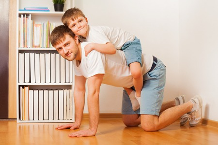 shoulder ride: Smiling boy enjoys riding on fathers back at home Stock Photo