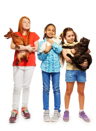 rabbit standing: Three diverse girls standing holding their beloved pets cat, rabbit and dog